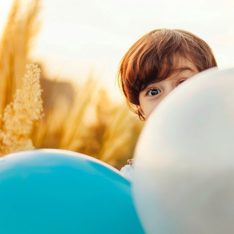 Child hiding behind balloons